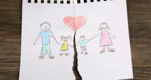 Kid's drawing of their family being torn apart on a wooden background.